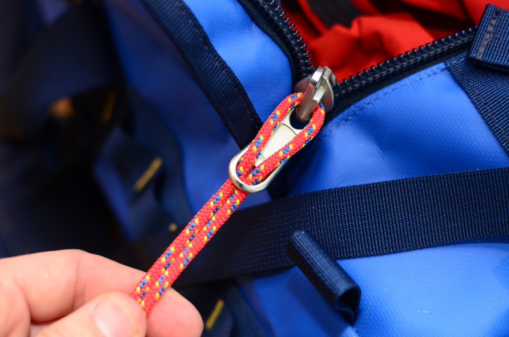 Pull the cord through the loose zipper part so both ends match up symmetrically